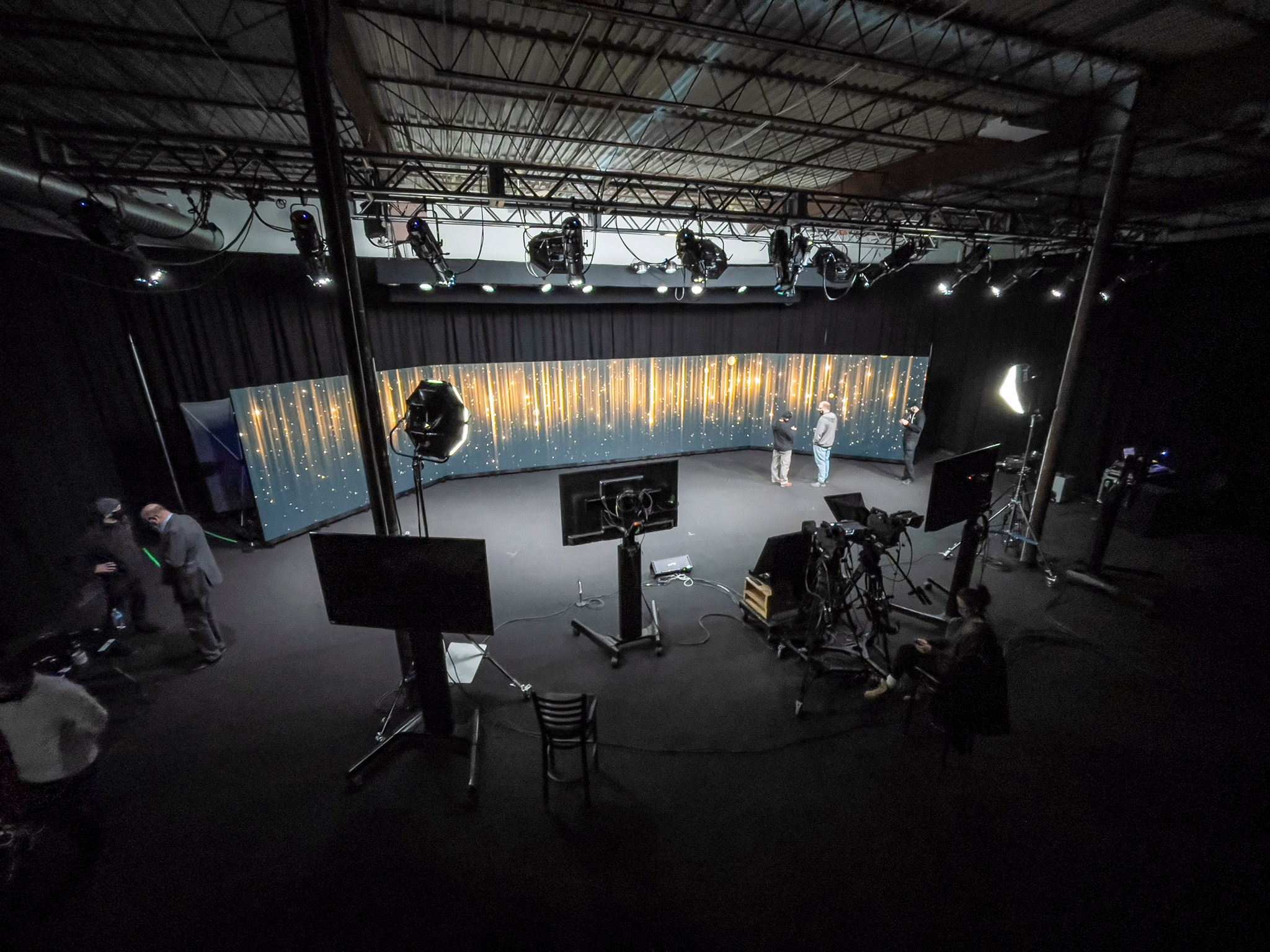 a hybrid events stage with teleprompters and video recording equipment