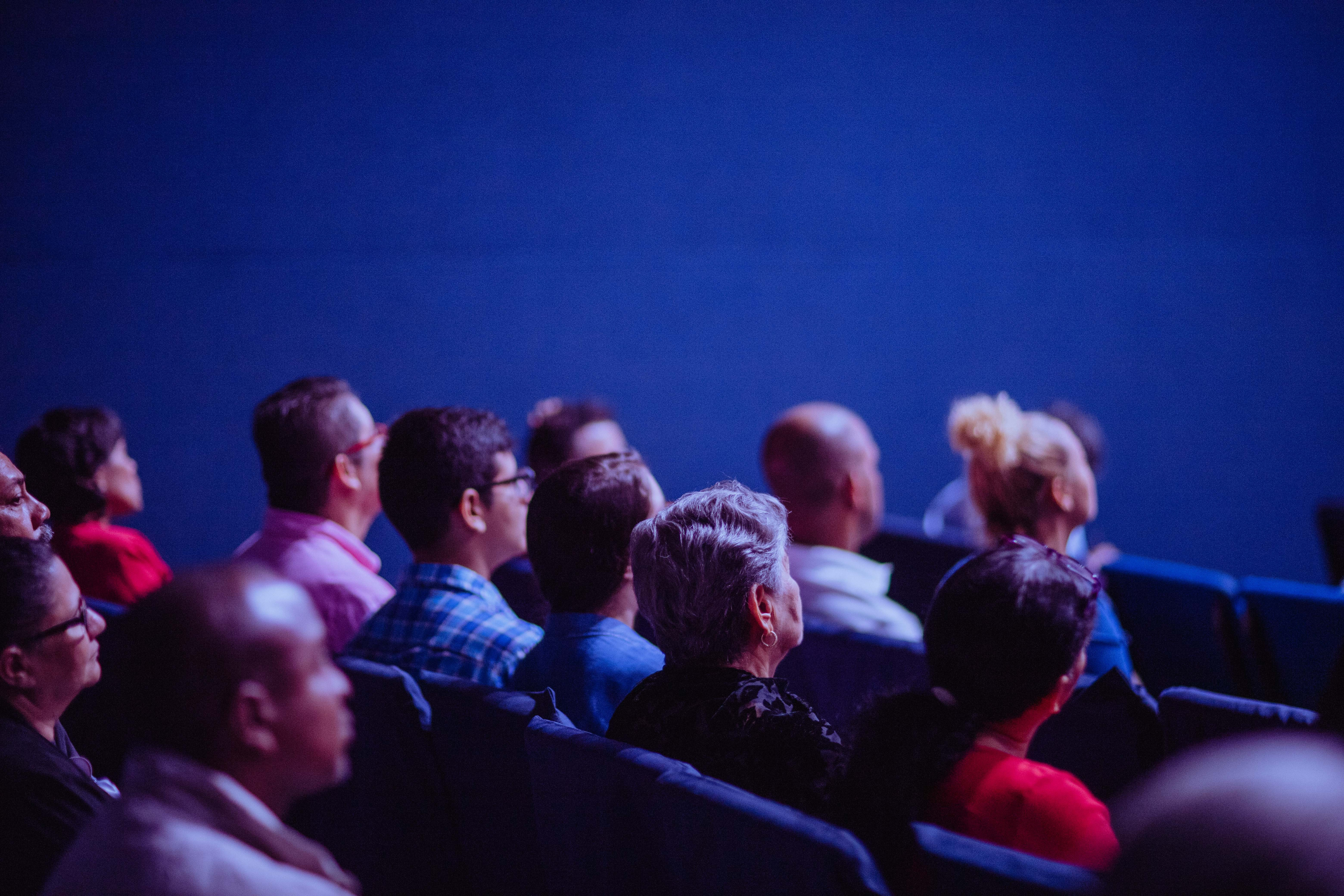 in-person audience watching a hybrid event on stage